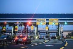 Bilar passerar till och med upplysta Telepass avgiftportar på den italienska huvudvägen arkivfoton