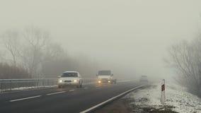 Bilar rider på vägen och de glänsande ljusen i dimman stock video