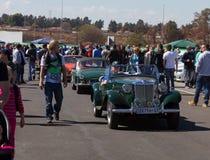 Bilar som kommer till och med folkmassan Royaltyfri Bild