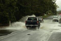 bilar som korsar den översvämmade vägen Royaltyfri Foto