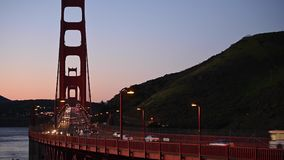 Bilar som korsar Golden Gate på solnedgången stock video