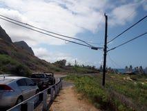Bilar som parkeras längs cliffsideberghuvudvägen på Makapuu med sträckning av det blåa Stilla havet arkivfoton