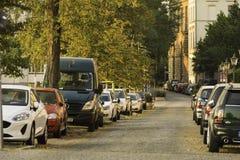 Bilar som parkeras längs en tyst gata på skymning i Dusseldorf, Tyskland royaltyfri bild