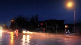 Bilar som passerar hus på natten i hällregn stock video