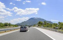 Bilar som rusar på autobahnen bland berglandskap Arkivbild