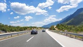 Bilar som rusar på autobahnen bland berglandskap Royaltyfri Bild