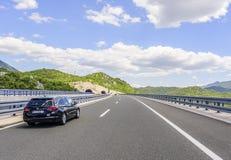 Bilar som rusar på autobahnen bland berglandskap Arkivbilder