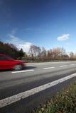 Bilar som snabbt flyttar sig på en huvudväg Arkivfoto