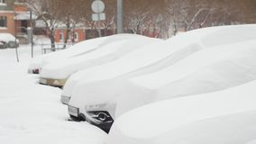 Bilar som täckas fullständigt med snö på parkering arkivfilmer