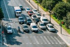 Bilar som väntar på trafikljus för att gångare ska korsa gatan Arkivbild