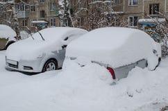 Bilar under snödrivor efter snöfall arkivbilder