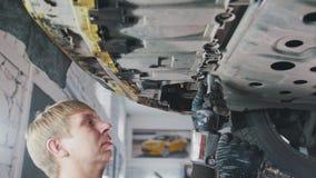 Bilautomatiskservice - mekanikern skruva av detaljen av bilen under botten av medlet royaltyfri foto