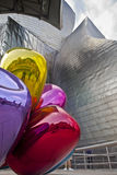 Bilbao Guggenheim museum. Part of Guggenheim museum in Bilbao,Spain and part of a colourful sculpture which is in front of the building Royalty Free Stock Photo