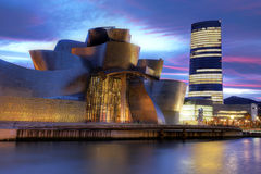 Bilbao, Spain. December 15, 2011: The Guggenheim Museum  under a dramatic sunset sky. In the background is the latest addition to Bilbao's skyline - the