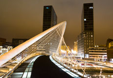 BILBAO, SPAIN - APRIL 02. Nightview of Zubizuri bridge and Isozaki towers in the background, in Bilbao, Spain, on April 02, 2012. The Zubizuri bridge was Stock Image