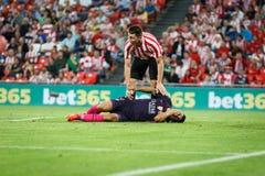 BILBAO SPANIEN - AUGUSTI 28: Luis Suarez FC Barcelonaspelare, på gräset som såras med Aymeric Laporte, Bilbao spelare, i det matt Arkivbild