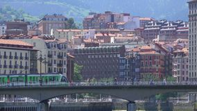Bilbao Tram travels across bridge with city behind it stock video footage