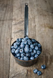 Bilberry. In an iron ladle on a wooden table Stock Photography