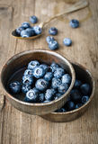 Bilberry. In iron bowls on a wooden table Stock Photos