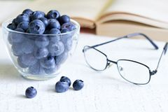 Bilberry cure for eyes concept with glasses. Closeup Stock Photography