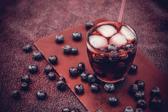 Bilberry drink with the berries and ice cubes. Na refreshing drink with ice and blueberry Stock Photography