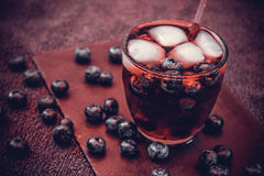 Bilberry drink with the berries and ice cubes. Na refreshing drink with ice and blueberry Stock Photos