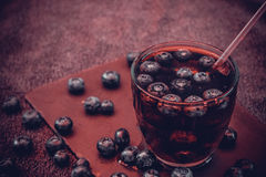 Bilberry drink with the berries and ice cubes. Na refreshing drink with ice and blueberry Royalty Free Stock Photos