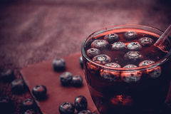 Bilberry drink with the berries and ice cubes. Na refreshing drink with ice and blueberry Royalty Free Stock Images