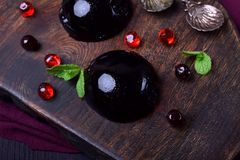 Bilberry hemisphere jelly. On a wooden board royalty free stock images