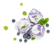 Bilberry ice cream, top view. Above view of scoops of blueberry ice cream fresh berries decorated with leaves of mint on white background Stock Photo