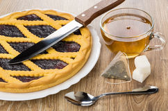Bilberry pie in dish, kitchen knife, tea in cup Stock Images