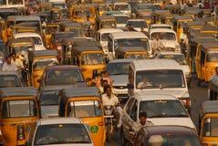 Bilbilar två person som drar en skottkärra som väntar på signalen i en trafik Fotografering för Bildbyråer