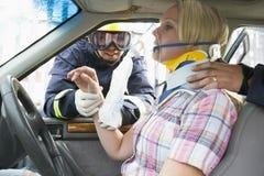 bilbrandmän som hjälper den sårada kvinnan Arkivbilder