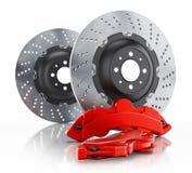 Bilbromsdiskett och röd klämma som isoleras på vit Arkivfoto