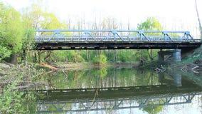 Bilbron över floden reflekteras i vatten i lugna vårdag Damm i skog lager videofilmer