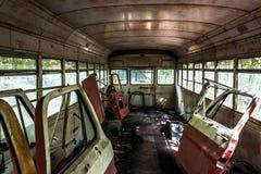 Bildörrar inom av en gammal skolbuss i en skrot arkivbilder