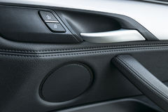 Bildörrhandtag inom den lyxiga moderna bilen med svart läder- och strömbrytareknappkontroll, moderna bilinredetaljer Royaltyfri Foto