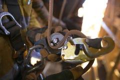 Bild Öffnungsunterlänge des Seilzugangs der männlichen Handund der Verbindungseinfügung des Ausschnitts mit abseiling Nylonseil n stockfotos