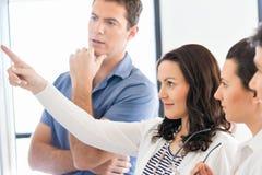Bild av affärspartners som diskuterar dokument och idéer arkivbilder