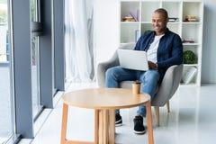Bild av afrikansk amerikanaffärsmannen som arbetar på hans bärbar dator Stilig ung man på hans skrivbord arkivbilder
