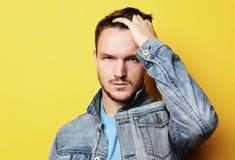 Bild av anseendet för ung man som isoleras över gul bakgrund L arkivfoton