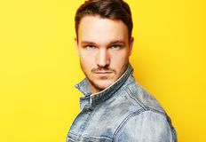 Bild av anseendet för ung man som isoleras över gul bakgrund L royaltyfri fotografi