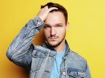 Bild av anseendet för ung man som isoleras över gul bakgrund L royaltyfri foto