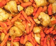 Bild av aptitretande stekt kycklingstycken med ljusa orange morötter med lökstycken i solrosolja Fotografering för Bildbyråer