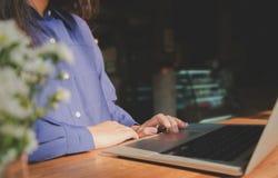 Bild av att använda för kvinnahänder/som skriver på utvald fokus för bärbar datordator på tangentbordet arkivbilder