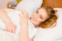 Bild av att koppla av den härliga flickan för blåa ögon för ung kvinna som blonda ligger på le en vit säng lycklig & seende kamer Fotografering för Bildbyråer
