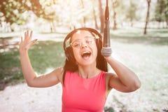 Bild av bärande hörlurar för emotionell flicka och lyssnande musik till och med den Också är hon sjungande till mikrofonen Fotografering för Bildbyråer