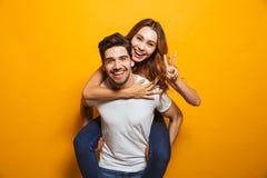 Bild av caucasian par som har gyckel medan man som piggybacking joyf royaltyfri fotografi