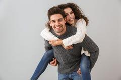 Bild av caucasian par som har gyckel- och stundmannen som piggybacking den glade kvinnan, över grå bakgrund arkivfoto