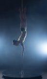 Bild av dansaren som hänger som är uppochnervänd på pylonen Royaltyfria Bilder